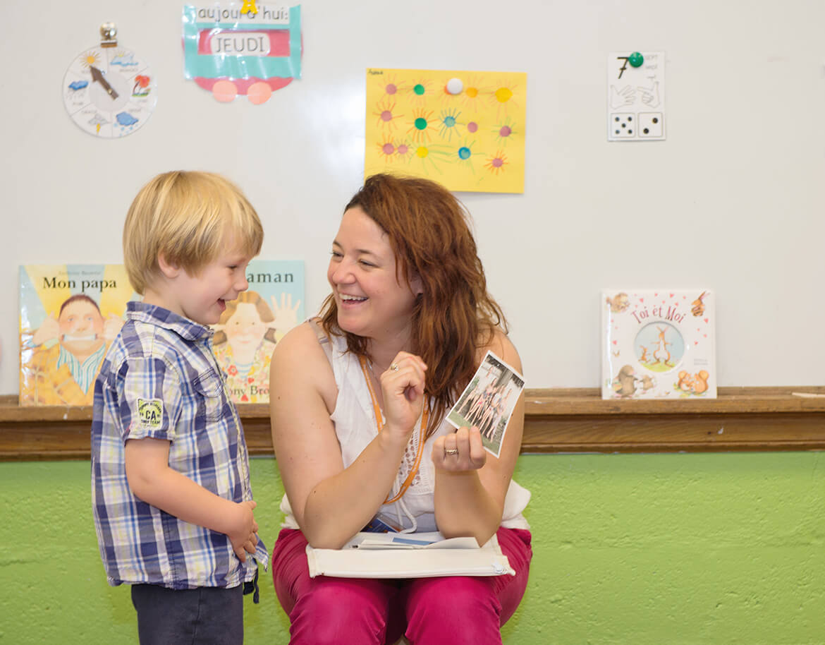 a preschooler of the French american academy and its teacher having a good time