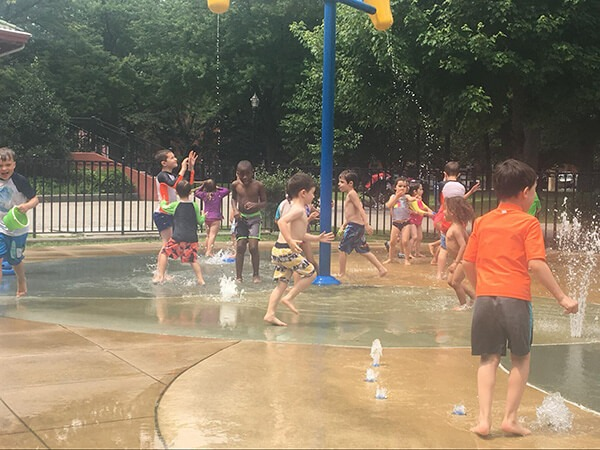 Kids playing at a water playground while at a summer camp at the French American Academy
