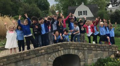 preschoolers on a stone bridge with their hands in the air