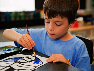 A young boy painting on a table in Elementary school