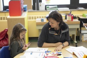 A teacher and a student at a table at the French american academy elementary school