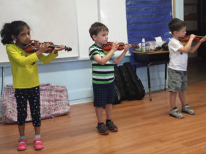 Kids from the French american academy playing music in an enrichment session