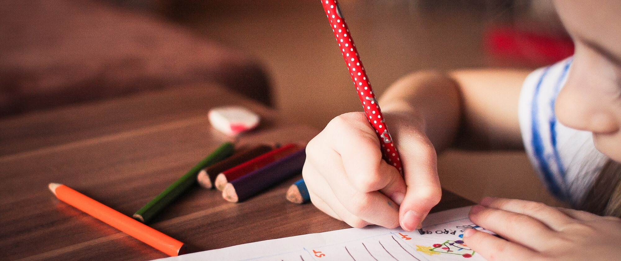 Picture of a child writing while his parents visit the school