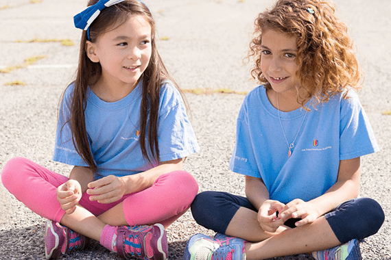 2 elementary schools girls from the French american academy sitting on the ground