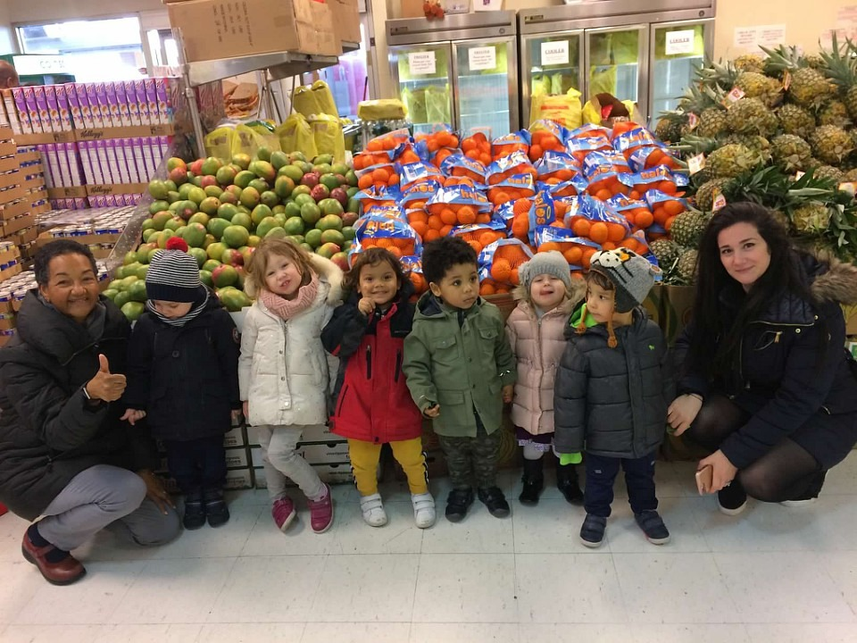 Pk2 in a store in front of fruit displays with their teachers