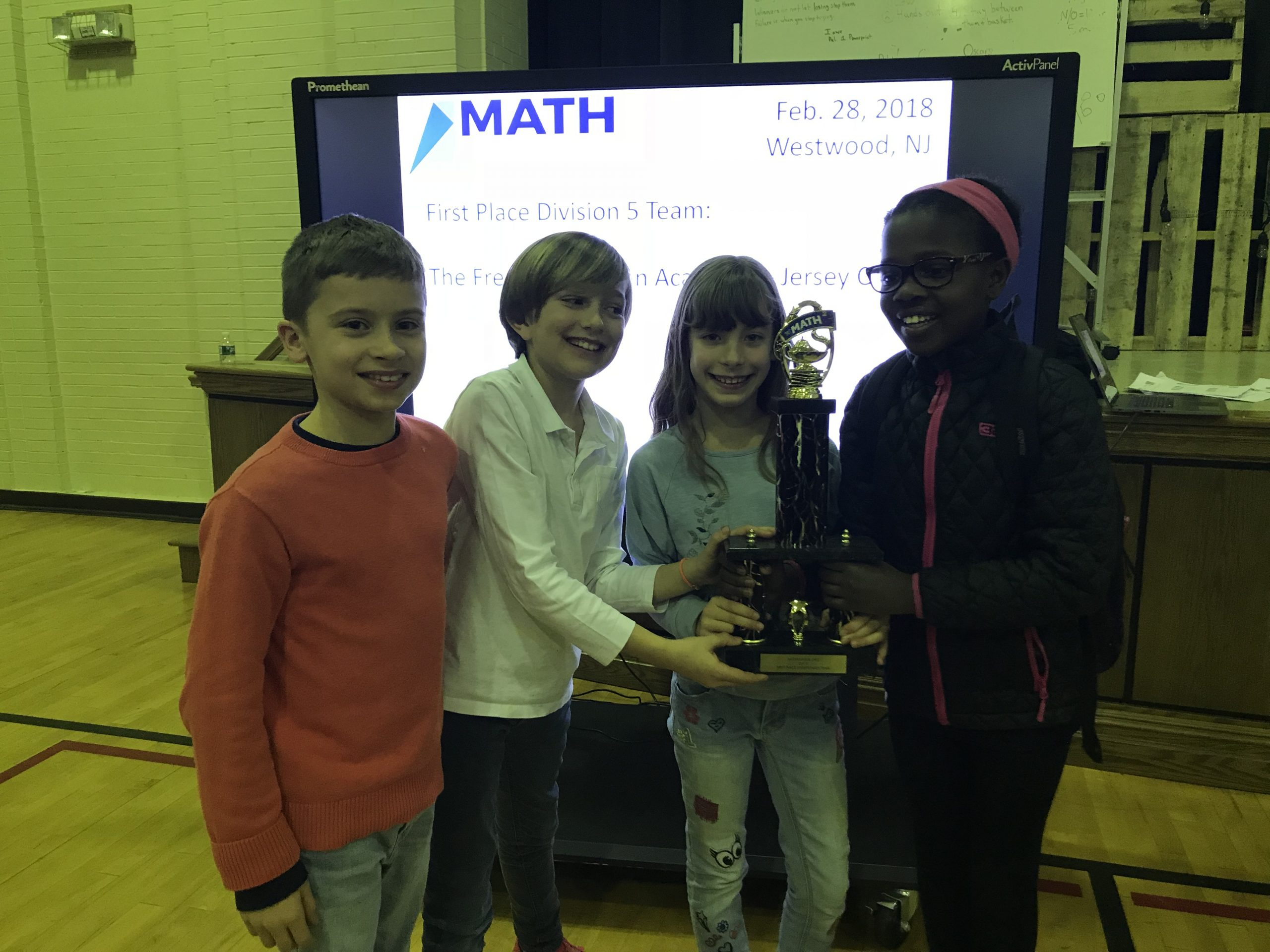 Elementary schoolers posing with their trophy after a win in a math competition