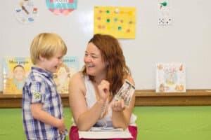 A preschooler laughing with his teacher