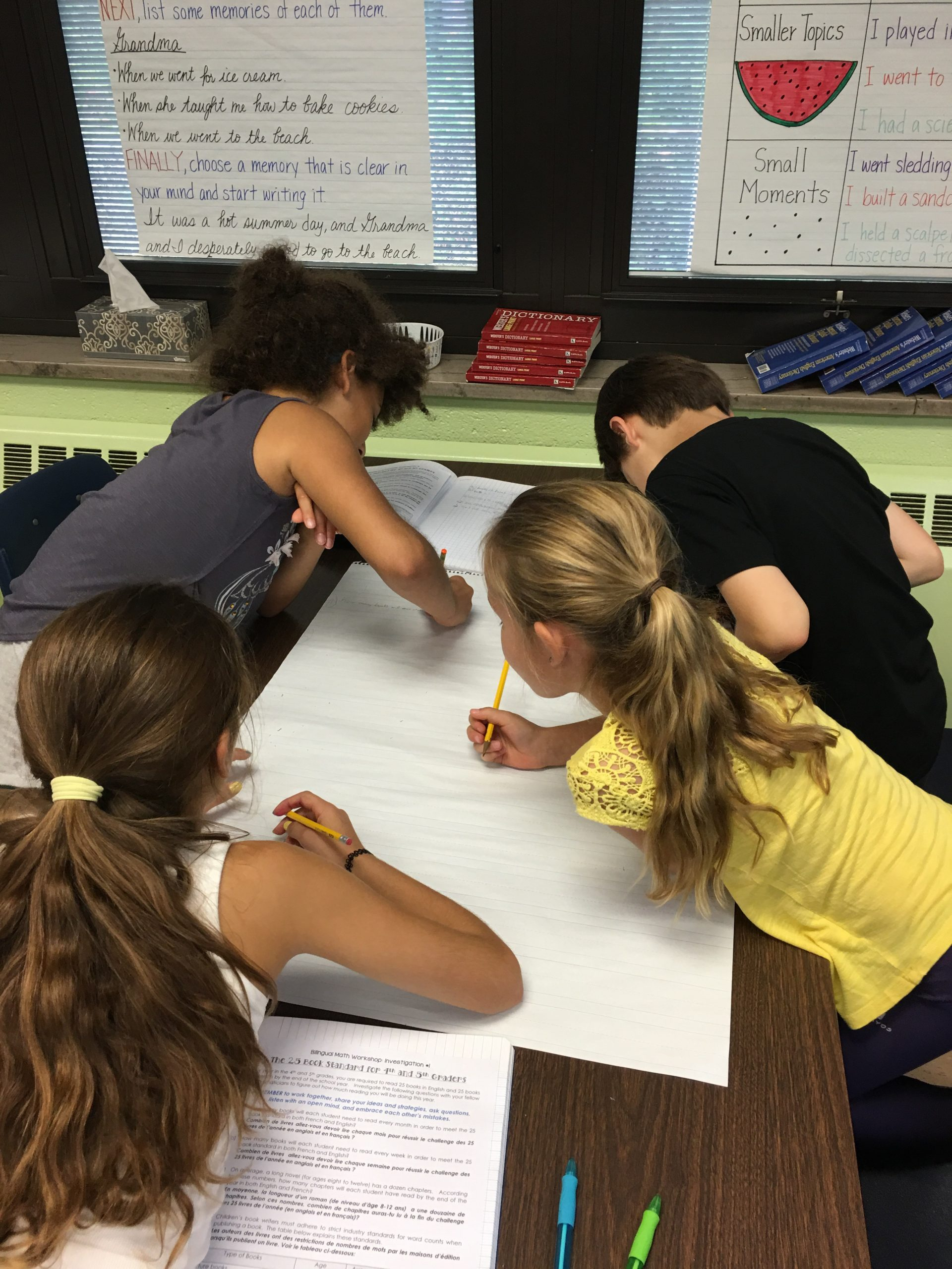Elementary schoolers working on a language arts project on the floor