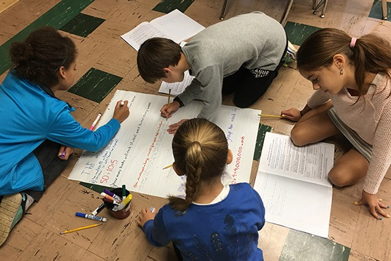 Elementary schoolers working on a math project on the floor