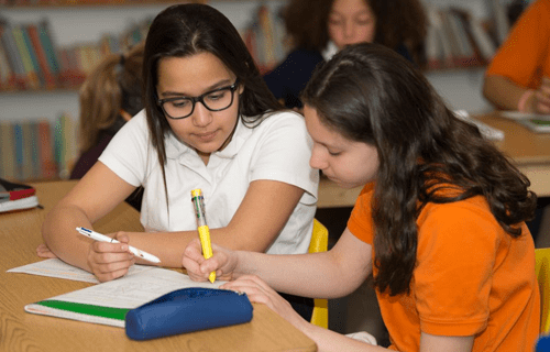 two middle schoolers at the French american academy working together to solve a problem