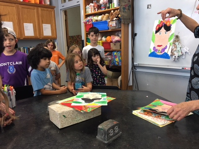 Students around a table in front of a teacher, experiencing the student-centered curriculum approach