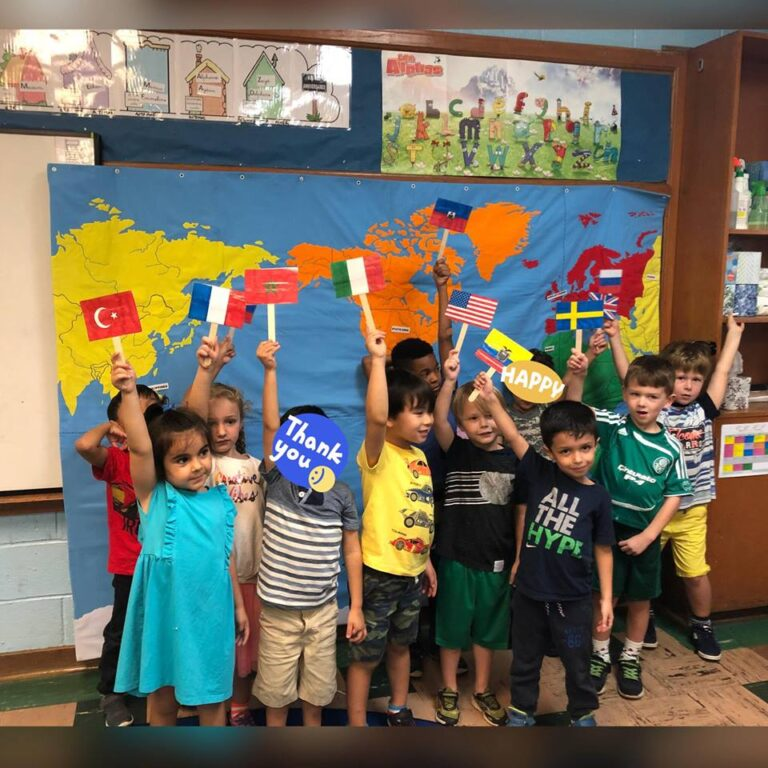 Preschoolers showing up their flags in front of a world map during international day at the French American Academy
