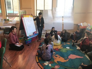 A teacher explaining Math beside a paper board and in front of children in Elementary school