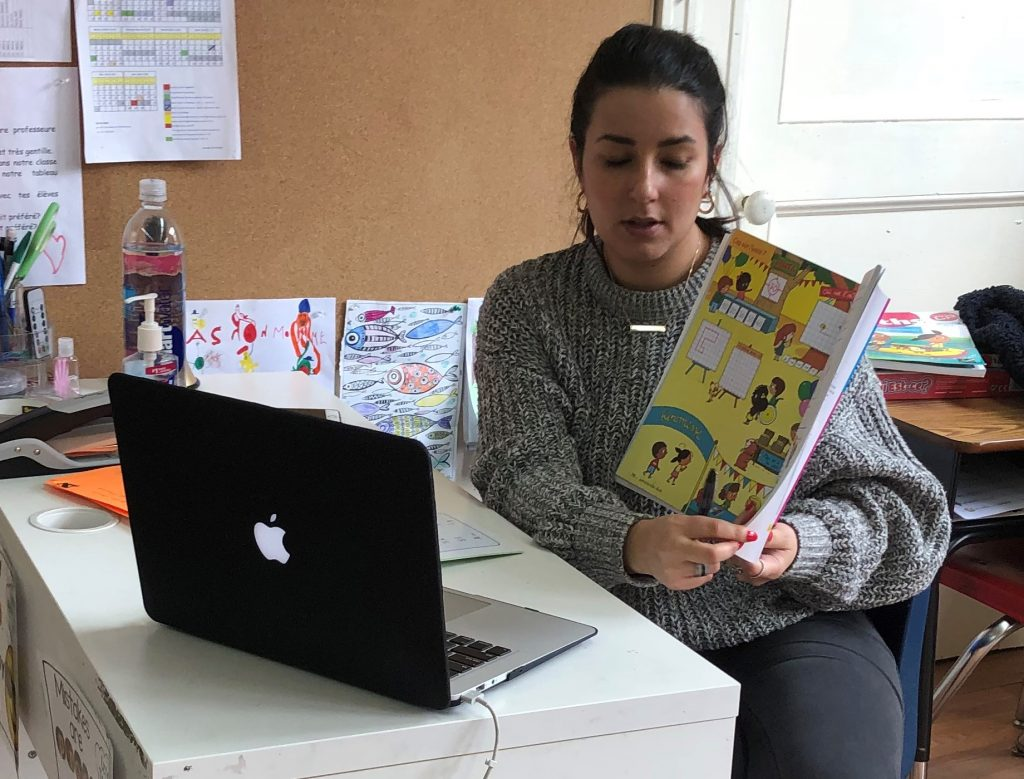 Teacher reading a book to her students through distant learning during covid19 school closure