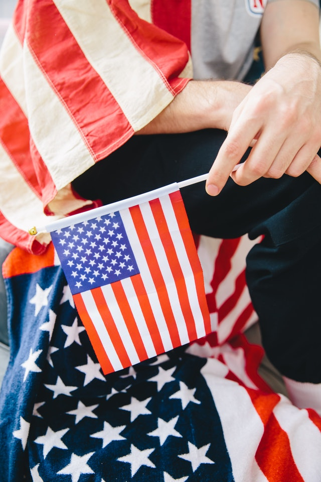 person arriving in the US holding an American flag