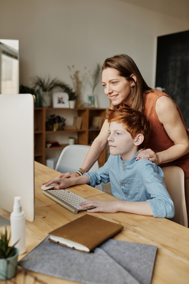 Parent helping her son with homework in front of his screen