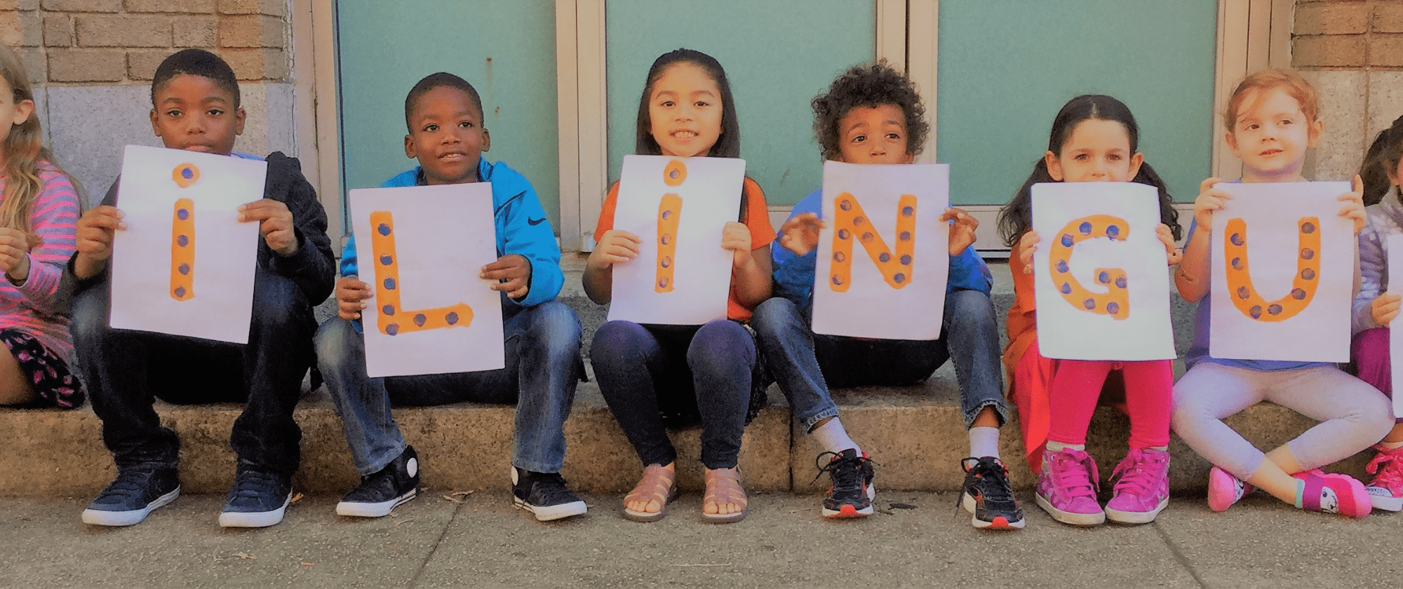 Kids showing letter panels forming the word Bilingual