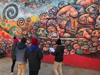 Students practicing Arts in front of a wall painting