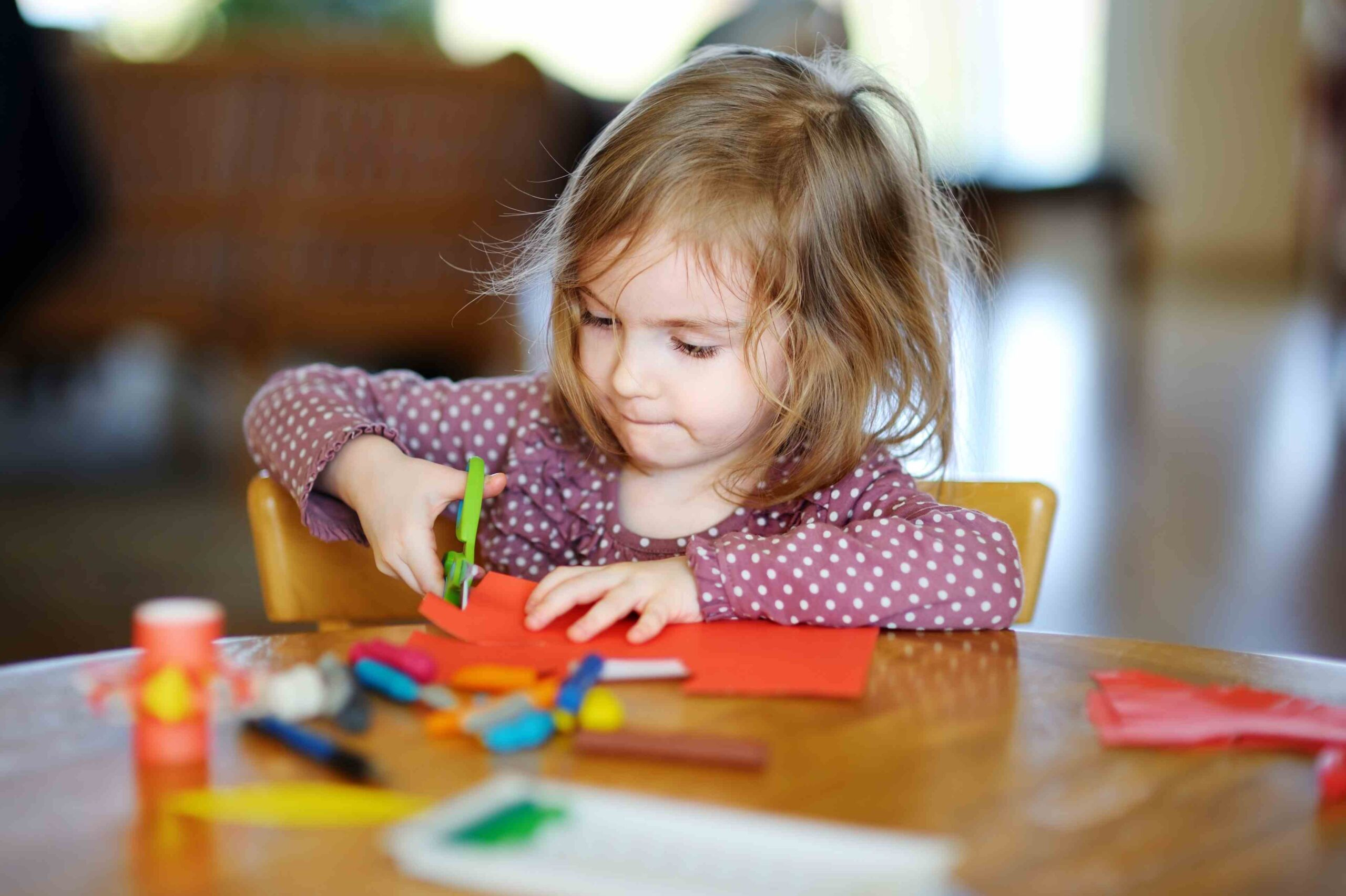 Preschooler at the French american academy performing a cutting on a table