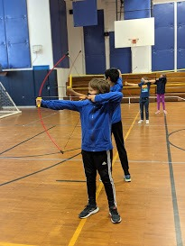 Student practicing archery with sport uniform at the French american academy