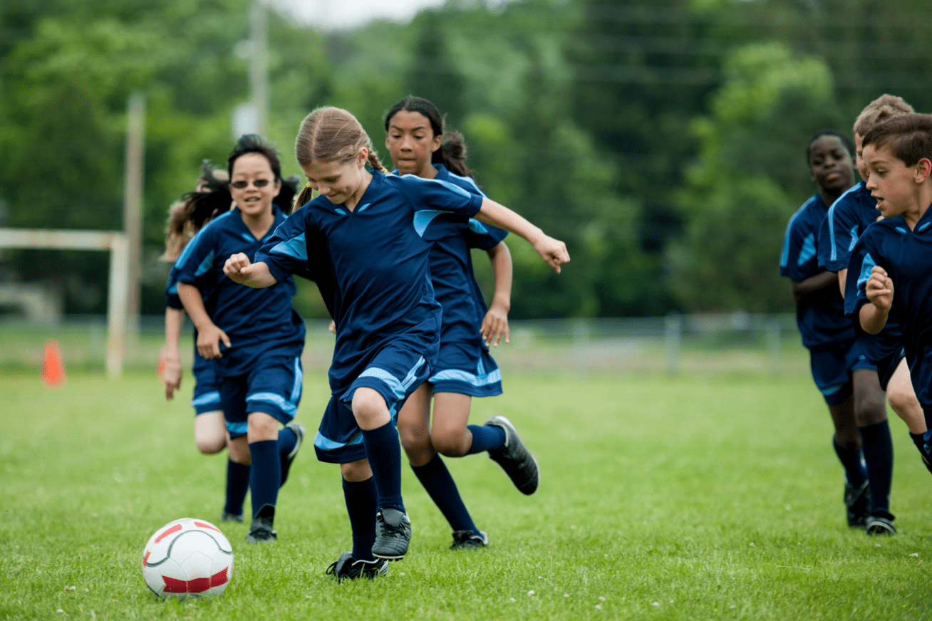 boys and girls playing soccer on a field