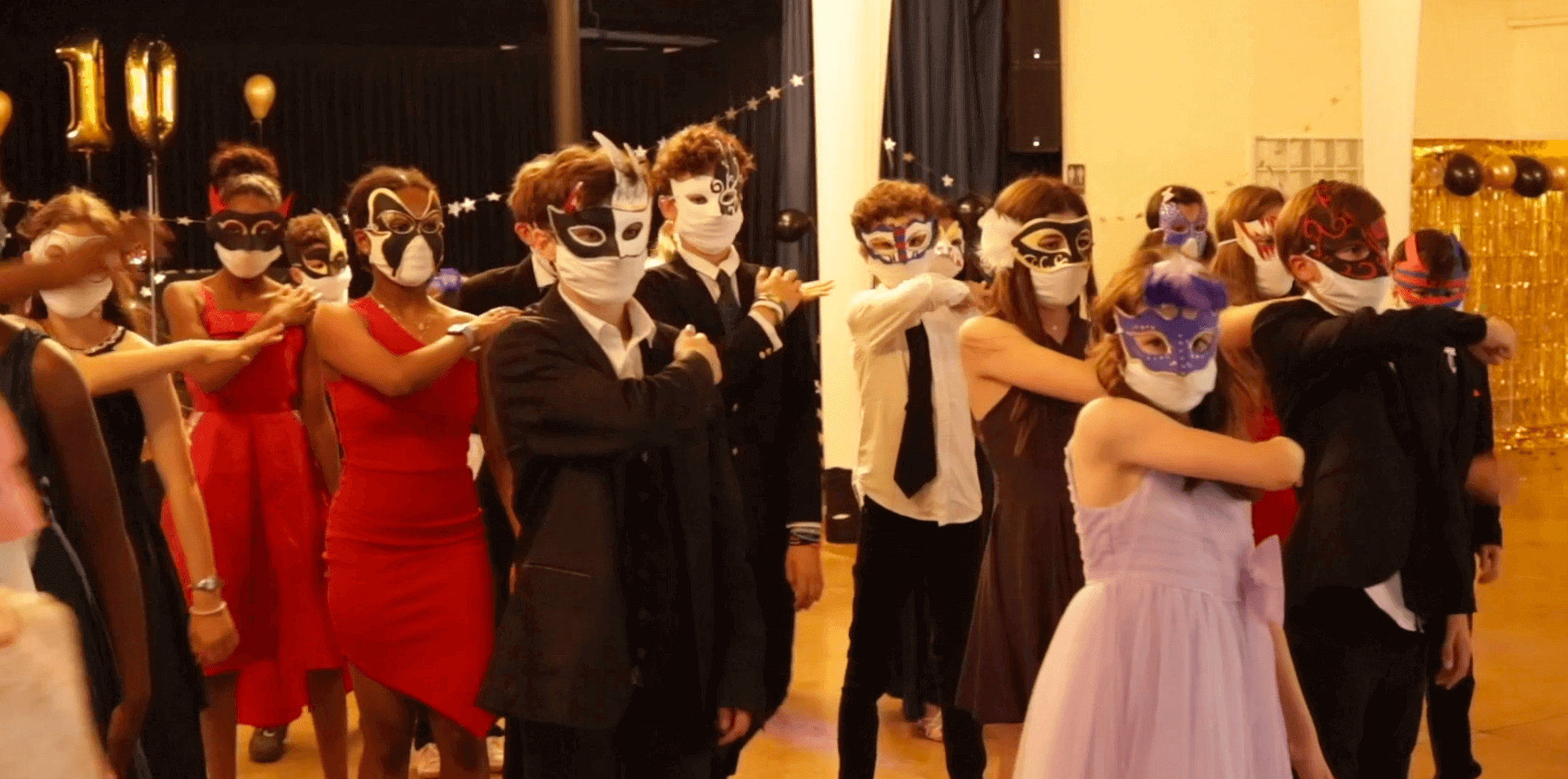 Many students wearing a costumed mask in the musical Face a Face
