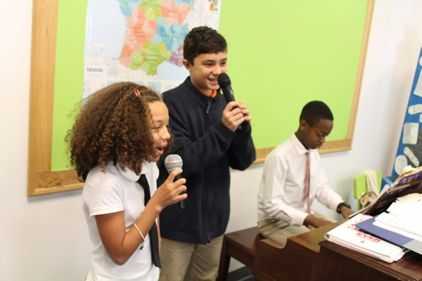 2 students of the French american academy performing a song in uniforms
