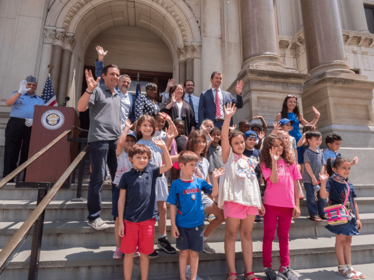 Kids, the mayor of Jersey City and the consul general of France on the stairs of Jersey City City hall on Bastille Day